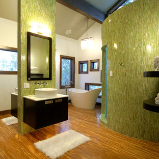 This is an example of a contemporary bathroom in Denver with a vessel sink, a freestanding tub and green walls.