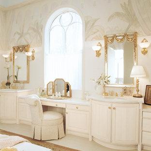 Modelo de cuarto de baño principal, clásico, grande, con paredes beige, lavabo bajoencimera, armarios con paneles con relieve, encimera de acrílico y puertas de armario beige