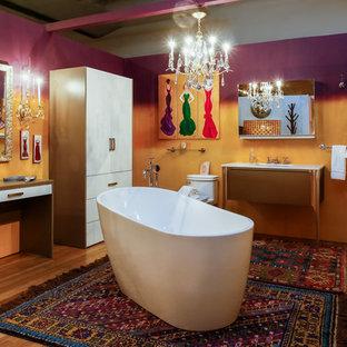 Diseño de cuarto de baño con ducha, bohemio, de tamaño medio, con armarios con paneles lisos, puertas de armario beige, bañera exenta, sanitario de una pieza, baldosas y/o azulejos marrones, paredes púrpuras, suelo de madera clara, lavabo bajoencimera y encimera de cuarcita