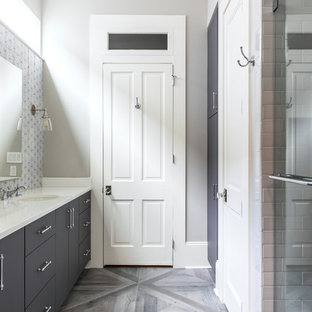 Mid-sized transitional master medium tone wood floor and gray floor alcove shower photo in New Orleans with flat-panel cabinets, gray cabinets, gray walls, an undermount sink, quartz countertops, a hinged shower door and white countertops
