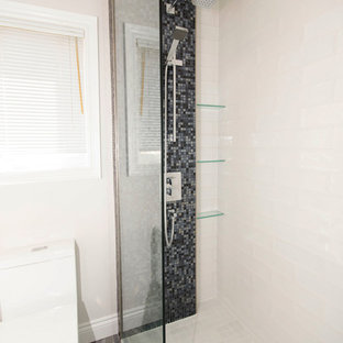 Diseño de cuarto de baño infantil, moderno, de tamaño medio, con armarios con paneles lisos, puertas de armario blancas, ducha empotrada, baldosas y/o azulejos grises, baldosas y/o azulejos en mosaico, paredes blancas, suelo de baldosas de porcelana, lavabo sobreencimera, encimera de cuarzo compacto, suelo gris, ducha con puerta con bisagras y sanitario de una pieza