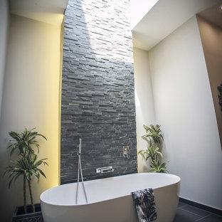 Idee per una stanza da bagno per bambini design di medie dimensioni con vasca freestanding, doccia aperta, pareti beige, doccia aperta, ante in legno bruno, piastrelle nere, piastrelle in ardesia, pavimento in gres porcellanato, lavabo a colonna, top in legno, pavimento beige e top nero