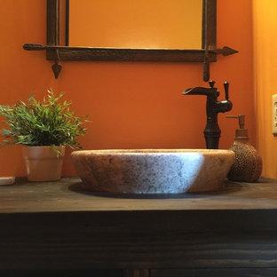 Idee per una stanza da bagno con doccia stile rurale di medie dimensioni con consolle stile comò, ante marroni, WC a due pezzi, pareti arancioni, lavabo a bacinella, top in legno, pavimento in legno massello medio e pavimento multicolore
