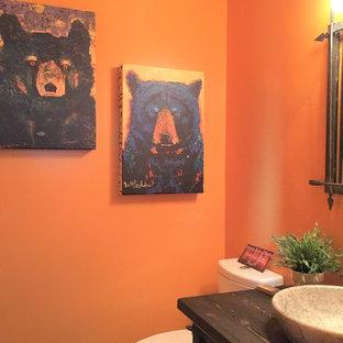 Diseño de cuarto de baño con ducha, rústico, de tamaño medio, con armarios tipo mueble, puertas de armario marrones, encimera de madera, sanitario de dos piezas, parades naranjas, lavabo sobreencimera, suelo de madera en tonos medios y suelo multicolor