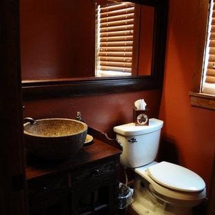 Foto de cuarto de baño con ducha, rural, de tamaño medio, con armarios tipo mueble, puertas de armario de madera en tonos medios, paredes rojas, suelo de madera oscura, lavabo sobreencimera, bañera esquinera, ducha abierta, sanitario de una pieza, baldosas y/o azulejos rojos, encimera de madera y ducha abierta