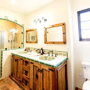 Foto di una stanza da bagno padronale mediterranea di medie dimensioni con ante con riquadro incassato, ante con finitura invecchiata, doccia alcova, WC a due pezzi, piastrelle verdi, piastrelle in ceramica, pareti bianche, pavimento in terracotta, lavabo da incasso e top piastrellato