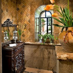 Foto di una stanza da bagno mediterranea di medie dimensioni con consolle stile comò, ante in legno bruno, top in legno, piastrelle in pietra, pareti multicolore, pavimento in mattoni e pavimento marrone