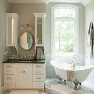 Exemple d'une petite salle de bain principale chic avec un carrelage gris, un placard avec porte à panneau surélevé, des portes de placard blanches, une baignoire sur pieds, un carrelage de pierre et un mur beige.