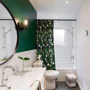 モントリオールの小さいモダンスタイルのおしゃれなバスルーム (浴槽なし) (フラットパネル扉のキャビネット、アルコーブ型浴槽、シャワー付き浴槽、一体型トイレ、白いタイル、緑の壁、セラミックタイルの床、珪岩の洗面台、白い洗面カウンター、グレーの床、淡色木目調キャビネット、サブウェイタイル、コンソール型シンク) の写真