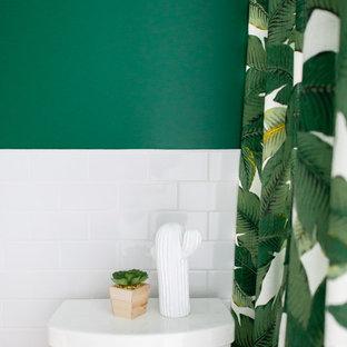モントリオールのモダンスタイルのおしゃれなバスルーム (浴槽なし) (フラットパネル扉のキャビネット、淡色木目調キャビネット、アルコーブ型浴槽、シャワー付き浴槽、一体型トイレ、白いタイル、サブウェイタイル、緑の壁、セラミックタイルの床、コンソール型シンク、珪岩の洗面台、グレーの床、白い洗面カウンター) の写真