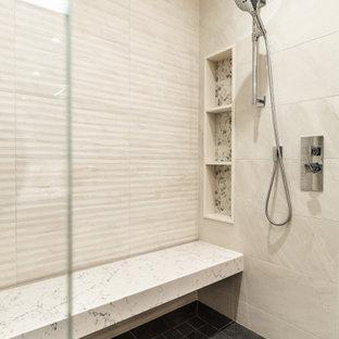 モントリオールの中くらいのコンテンポラリースタイルのおしゃれなマスターバスルーム (フラットパネル扉のキャビネット、中間色木目調キャビネット、ドロップイン型浴槽、ダブルシャワー、壁掛け式トイレ、ベージュのタイル、スレートタイル、ベージュの壁、スレートの床、アンダーカウンター洗面器、クオーツストーンの洗面台、グレーの床、開き戸のシャワー、白い洗面カウンター、シャワーベンチ、洗面台2つ、造り付け洗面台、板張り壁) の写真