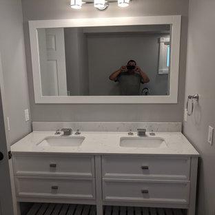 他の地域の巨大なトラディショナルスタイルのおしゃれなマスターバスルーム (落し込みパネル扉のキャビネット、白いキャビネット、置き型浴槽、アルコーブ型シャワー、分離型トイレ、グレーの壁、クッションフロア、アンダーカウンター洗面器、大理石の洗面台、グレーの床、引戸のシャワー、マルチカラーの洗面カウンター) の写真