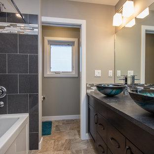 Diseño de cuarto de baño principal, actual, de tamaño medio, con armarios estilo shaker, puertas de armario de madera en tonos medios, bañera empotrada, combinación de ducha y bañera, baldosas y/o azulejos grises, baldosas y/o azulejos de vidrio, paredes grises, suelo de piedra caliza, lavabo sobreencimera y encimera de zinc