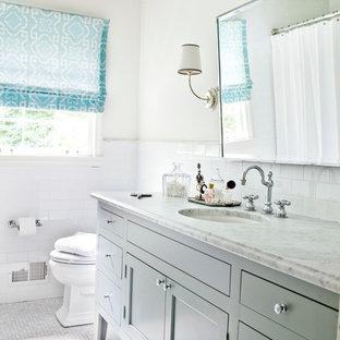 Foto di una stanza da bagno minimal con lavabo sottopiano, ante con riquadro incassato, ante grigie e piastrelle bianche