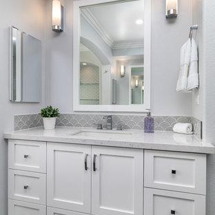 Idee per una grande stanza da bagno padronale stile shabby con ante in stile shaker, ante bianche, vasca freestanding, piastrelle grigie, piastrelle di vetro, pareti bianche, pavimento in gres porcellanato, lavabo sottopiano, top in quarzo composito, pavimento grigio e top bianco