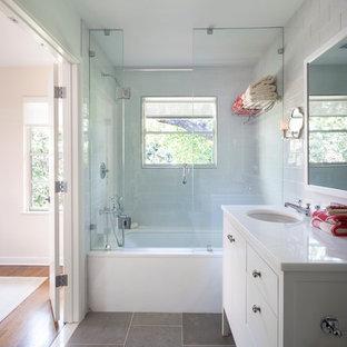 Klassisk inredning av ett badrum, med ett undermonterad handfat, vita skåp, ett undermonterat badkar, en dusch/badkar-kombination, grå kakel, stenkakel och släta luckor