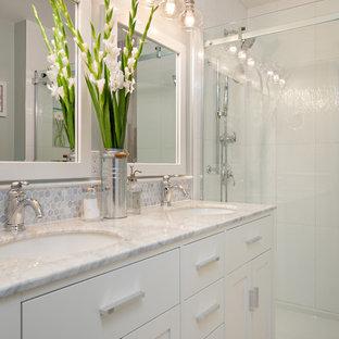 Inredning av ett klassiskt litet badrum, med ett undermonterad handfat, skåp i shakerstil, vita skåp, marmorbänkskiva, en dusch i en alkov, grå kakel, porslinskakel, grå väggar och klinkergolv i porslin