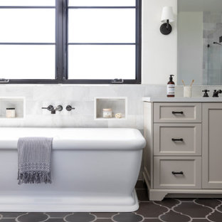 Inspiration for a mediterranean bathroom in Los Angeles with recessed-panel cabinets, grey cabinets, a freestanding bath, white walls, brown floors, white worktops, a built in vanity unit, a wall niche and a single sink.