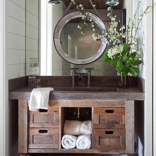 Modelo de cuarto de baño con ducha, de estilo de casa de campo, de tamaño medio, con armarios tipo mueble, puertas de armario con efecto envejecido, paredes blancas, suelo de madera en tonos medios, lavabo integrado, suelo marrón y encimera de cobre