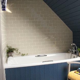 Modelo de cuarto de baño infantil, campestre, pequeño, con bañera encastrada, sanitario de dos piezas, baldosas y/o azulejos beige, baldosas y/o azulejos de cerámica, paredes azules, suelo laminado, lavabo con pedestal y suelo gris