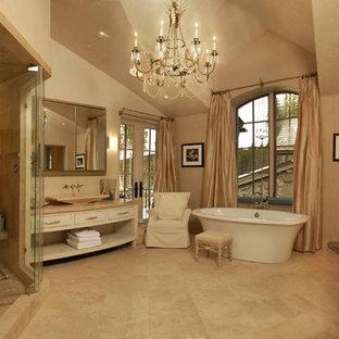 Foto di una stanza da bagno rustica con vasca freestanding, lavabo a bacinella e piastrelle in travertino