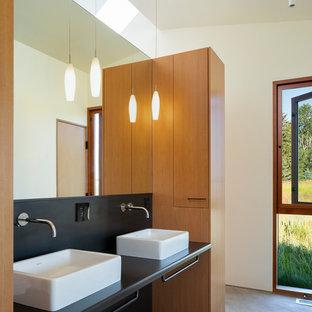 Создайте стильный интерьер: главная ванная комната среднего размера в современном стиле с плоскими фасадами, фасадами цвета дерева среднего тона, черной плиткой, металлической плиткой, белыми стенами, бетонным полом, настольной раковиной, столешницей из нержавеющей стали, серым полом и черной столешницей - последний тренд