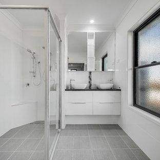 Bild på ett mellanstort funkis svart svart badrum, med släta luckor, vita skåp, svart och vit kakel, keramikplattor, vita väggar, ett fristående handfat, grått golv, en dusch i en alkov och dusch med skjutdörr