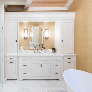 Idee per una grande stanza da bagno padronale chic con ante a filo, ante bianche, vasca freestanding, doccia alcova, piastrelle a specchio, pareti gialle, pavimento in marmo, lavabo sottopiano, top in quarzite, pavimento bianco e porta doccia a battente
