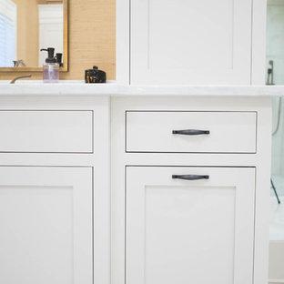 Immagine di una grande stanza da bagno padronale chic con ante a filo, ante bianche, vasca freestanding, doccia alcova, piastrelle a specchio, pareti gialle, pavimento in marmo, lavabo sottopiano, top in quarzite, pavimento bianco e porta doccia a battente
