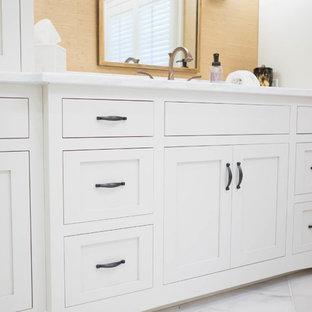 Ispirazione per una grande stanza da bagno padronale classica con ante a filo, ante bianche, vasca freestanding, doccia alcova, piastrelle a specchio, pareti gialle, pavimento in marmo, lavabo sottopiano, top in quarzite, pavimento bianco e porta doccia a battente