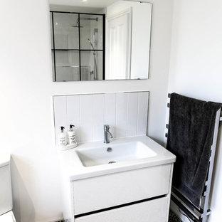 Mittelgroßes Shabby-Style Duschbad mit verzierten Schränken, weißen Schränken, Nasszelle, Wandtoilette mit Spülkasten, weißen Fliesen, Keramikfliesen, weißer Wandfarbe, Keramikboden, integriertem Waschbecken, Mineralwerkstoff-Waschtisch, schwarzem Boden, offener Dusche und weißer Waschtischplatte in Essex