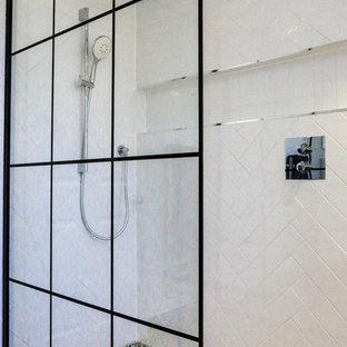 Mittelgroßes Shabby-Look Duschbad mit verzierten Schränken, weißen Schränken, Nasszelle, Wandtoilette mit Spülkasten, weißen Fliesen, Keramikfliesen, weißer Wandfarbe, Keramikboden, integriertem Waschbecken, Mineralwerkstoff-Waschtisch, schwarzem Boden, offener Dusche und weißer Waschtischplatte in Essex