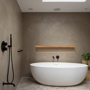 Diseño de cuarto de baño ecléctico, sin sin inodoro, con armarios con paneles lisos, puertas de armario grises, bañera exenta, sanitario de pared, paredes grises, suelo de baldosas de porcelana, lavabo encastrado, encimera de cemento, suelo gris, ducha abierta y encimeras grises