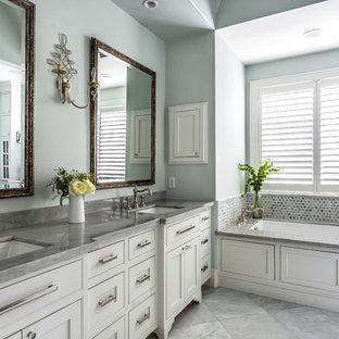 Diseño de cuarto de baño principal, tradicional, con armarios con rebordes decorativos, puertas de armario blancas, bañera encastrada sin remate, baldosas y/o azulejos de metal, paredes azules, lavabo bajoencimera y suelo gris