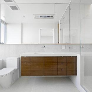 Réalisation d'une salle de bain minimaliste de taille moyenne avec un lavabo encastré, un placard à porte plane, des portes de placard en bois brun, un WC à poser, une baignoire encastrée, une douche d'angle, un mur blanc, un plan de toilette en quartz modifié et un plan de toilette blanc.