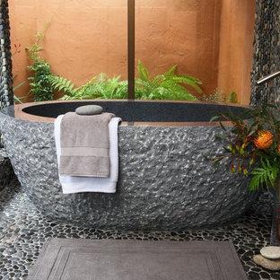 Immagine di una stanza da bagno mediterranea con vasca freestanding, piastrelle di ciottoli e pavimento con piastrelle di ciottoli