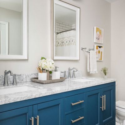 Inspiration for a large timeless kids' white tile and porcelain tile porcelain tile and gray floor bathroom remodel in Charlotte with shaker cabinets, blue cabinets, a two-piece toilet, gray walls, an undermount sink, marble countertops and gray countertops