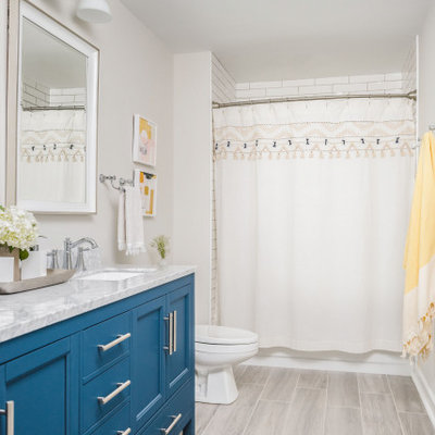 Large elegant kids' white tile and porcelain tile porcelain tile and gray floor bathroom photo in Charlotte with shaker cabinets, blue cabinets, a two-piece toilet, gray walls, an undermount sink, marble countertops and gray countertops