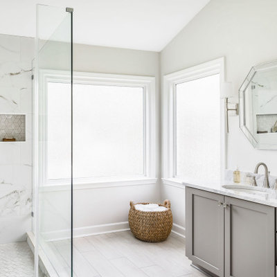 Large elegant master white tile and porcelain tile porcelain tile and beige floor corner shower photo in Charlotte with shaker cabinets, gray cabinets, a two-piece toilet, white walls, an undermount sink, marble countertops, a hinged shower door and gray countertops