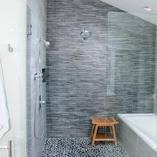 Modelo de cuarto de baño principal, clásico renovado, grande, con armarios con paneles lisos, puertas de armario de madera clara, bañera esquinera, ducha empotrada, sanitario de dos piezas, baldosas y/o azulejos blancos, paredes blancas, suelo de baldosas de cerámica y lavabo bajoencimera
