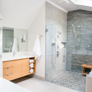 Inspiration for a large transitional master pebble tile and gray tile ceramic floor alcove shower remodel in Portland Maine with flat-panel cabinets, an undermount sink, light wood cabinets, a two-piece toilet, white walls, an undermount tub and a hinged shower door