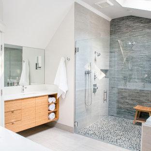 ポートランド(メイン)の広いトランジショナルスタイルのおしゃれなマスターバスルーム (フラットパネル扉のキャビネット、石タイル、アンダーカウンター洗面器、淡色木目調キャビネット、アルコーブ型シャワー、分離型トイレ、白い壁、セラミックタイルの床、グレーのタイル、アンダーマウント型浴槽、開き戸のシャワー) の写真