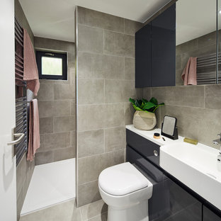 Photo of a contemporary shower room bathroom in London with flat-panel cabinets, black cabinets, an alcove shower, a wall mounted toilet, grey tiles, grey walls, grey floors and white worktops.