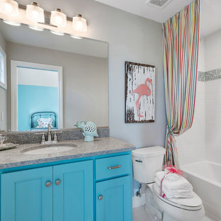 This is an example of a mid-sized beach style kids bathroom in Chicago with turquoise cabinets and an undermount sink.