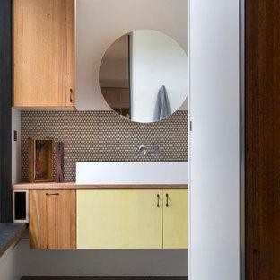 Новые идеи обустройства дома: ванная комната в современном стиле с столешницей из дерева, настольной раковиной, плоскими фасадами, желтыми фасадами и коричневой столешницей