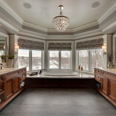 Drop-in bathtub - traditional black tile drop-in bathtub idea in Minneapolis with an undermount sink and dark wood cabinets