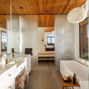 Ispirazione per una sauna contemporanea con ante lisce, ante bianche, vasca freestanding, doccia a filo pavimento, WC monopezzo, lastra di vetro, pareti bianche, lavabo sottopiano, top in marmo e porta doccia scorrevole