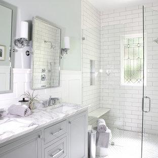 Aménagement d'une petit salle de bain classique avec des portes de placard grises, une douche à l'italienne, un carrelage blanc, un carrelage métro, un mur gris, un lavabo encastré, un plan de toilette en marbre, un sol blanc, une cabine de douche à porte battante, un plan de toilette blanc, un placard avec porte à panneau encastré, un sol en carrelage de terre cuite, un banc de douche et meuble double vasque.