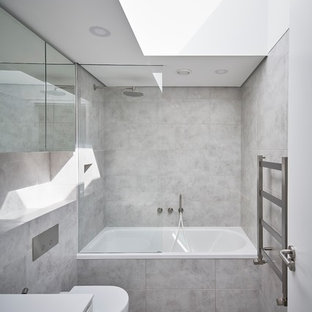 This is an example of a medium sized contemporary family bathroom in London with a built-in bath, a shower/bath combination, a one-piece toilet, grey tiles, a wall-mounted sink and tiled worktops.