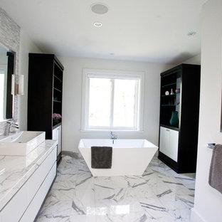 Immagine di una grande stanza da bagno padronale moderna con vasca freestanding, top in marmo, lavabo a bacinella, ante lisce, ante bianche, piastrelle bianche, piastrelle in pietra, pareti grigie e pavimento in marmo